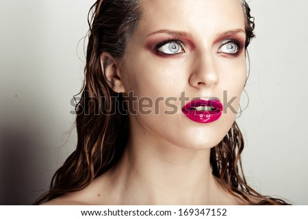 Beautiful girl with a purple lip makeup, clean shiny skin and wet hairstyle, bright eyes. Beauty fashion portrait of a woman face.
