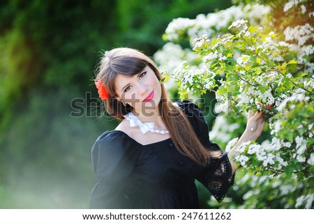 beautiful girl with a red bow in the spring flowery park. - stock photo