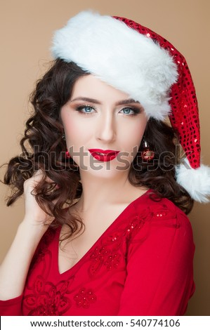 Beautiful girl with a red lipstick in the hat of Santa Claus, New Year, Merry Christmas