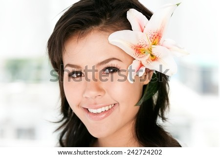 Beautiful girl with a tropical flower in her hair - stock photo