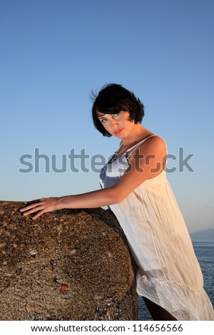 beautiful girl with a white dress on the wall of a fortress by the sea - stock photo