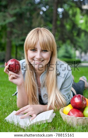 beautiful girl with an apple and reading a book on the grass