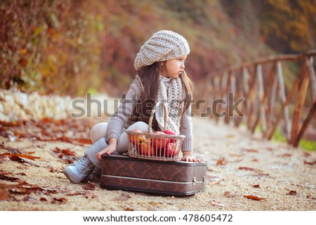 Beautiful girl with an old suitcase and apples on the road.