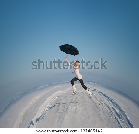 beautiful girl with an umbrella flies over the land round - stock photo