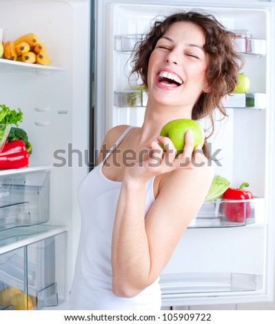 Beautiful Girl With Apple.Healthy Eating Concept .Diet. Beautiful Young Woman near the Refrigerator with healthy food. Fruits and Vegetables
