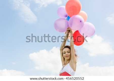 beautiful girl with balloons flying in the sky - stock photo