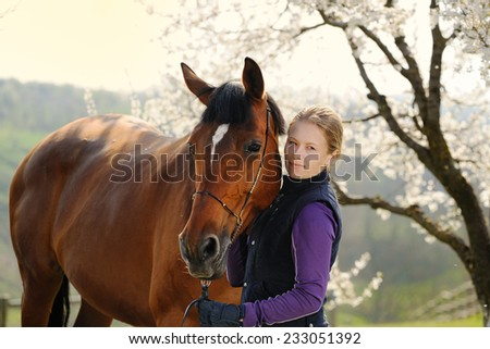 Beautiful girl with bay horse in spring garden - stock photo