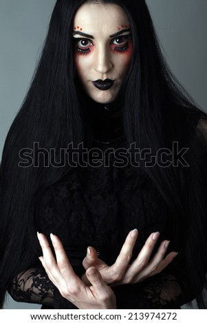 beautiful girl with black hair with artistic makeup and black lipstick in fetish and retro style, photographed in the studio - stock photo