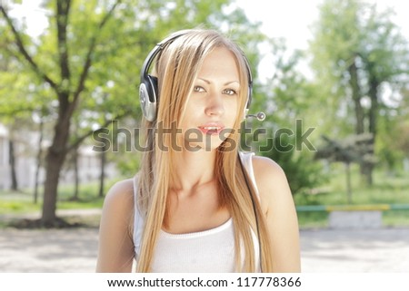 beautiful girl with blond hair, listening to music on headphones - stock photo