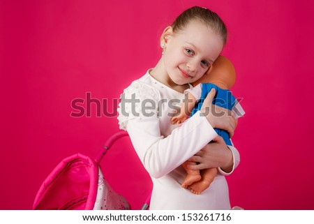 beautiful girl with blond hair swayed doll to sleep. close-up. mimics mom - stock photo