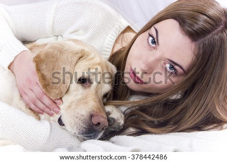 Beautiful girl with blue eyes and brown hair lying in bed and hugging her dog labrador retriever