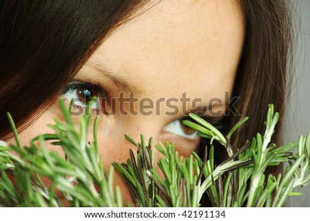 Beautiful girl with bright eyes sniffing rosemary - stock photo