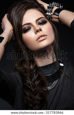 Beautiful girl with bright smokey make-up, perfect skin, black clothes, metal accessories and hairstyle as a braid. Picture taken in the studio on a gray background - stock photo