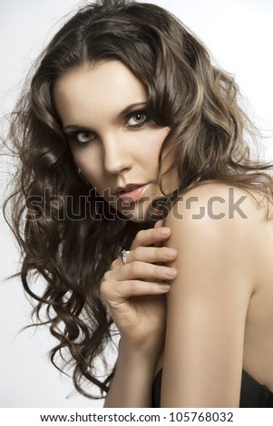 beautiful girl with brown, curly and long hair, she is turned of three quarters, looks in to the lens and her right hand is on the left shoulder