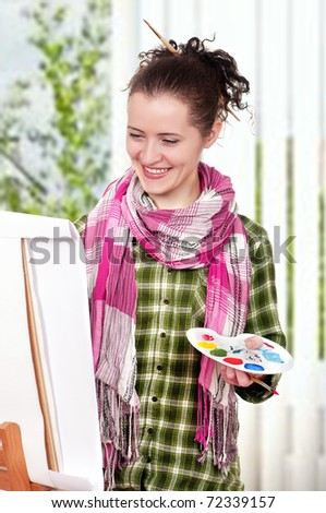 Beautiful girl with brushes near easel, painting on canvas.