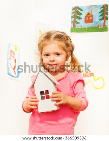 Beautiful girl with cardboard white doll house - stock photo