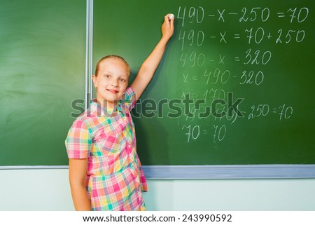 Beautiful girl with chalk in her hand writing mathematics equation looking straight in front of blackboard during mathematics lesson