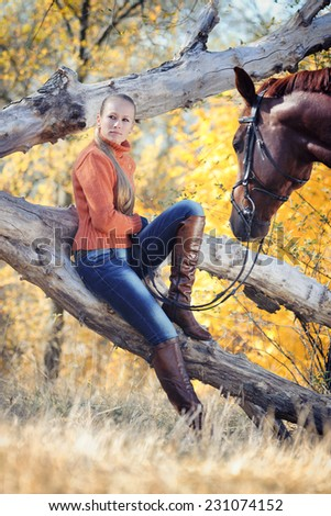 Beautiful girl with chestnut horse in autumn forest. Toned image - stock photo
