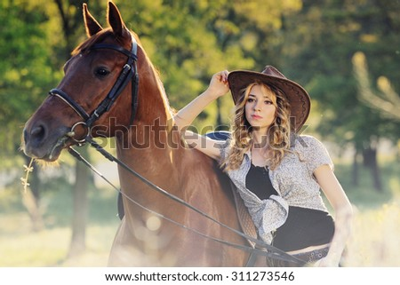 Beautiful girl with chestnut horse in summer field - stock photo