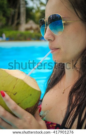 Beautiful girl with coconut cocktail, attractive young woman having refresh - stock photo