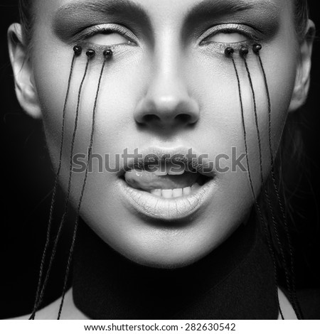 Beautiful girl with creative make-up in Gothic style and the threads of eyes. Art beauty face. Picture taken in the studio on a black background. Black and white photo - stock photo