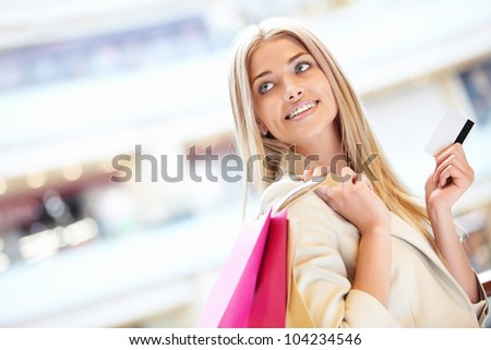 Beautiful girl with credit card at the store - stock photo