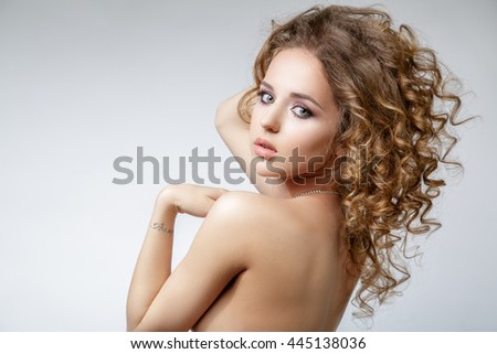 Beautiful girl with curly blond hair looking over her shoulder at the camera. She has big eyes, long eyelashes, a necklace around his neck and a tattoo on her arm. - stock photo