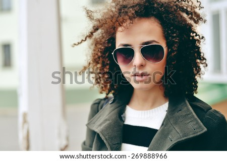 Beautiful girl with curly hair in sunglasses. Close up - stock photo