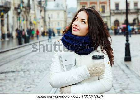 Beautiful girl, with curly long hair, wearing in white coat, blue scarf and gloves, holding cup of coffee and magazine and looking up, on the street of old European city, waist up - stock photo