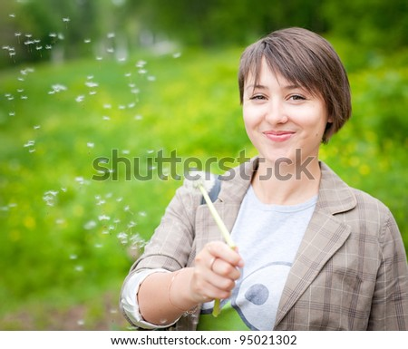 beautiful Girl with dandelion on green field - stock photo