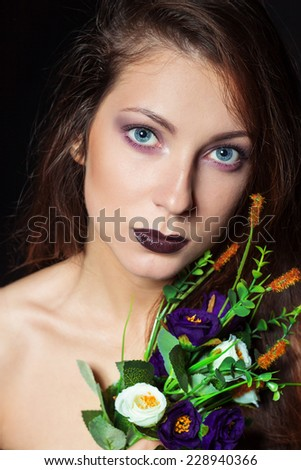 beautiful girl with dark hair and bright make-up with a bouquet of purple flowers in the Studio on a black background. new year's makeup, blue eyes