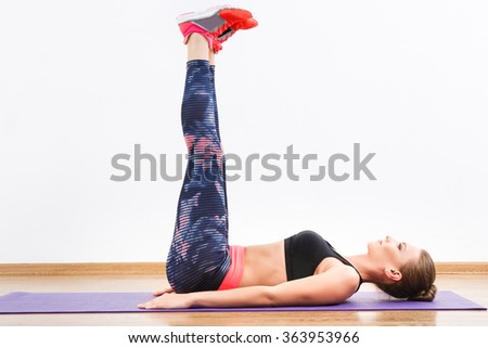 Beautiful girl with dark hair wearing pink snickers, dark leggings and black short top doing leg raise at gym, fitness, white wall and wooden floor. - stock photo