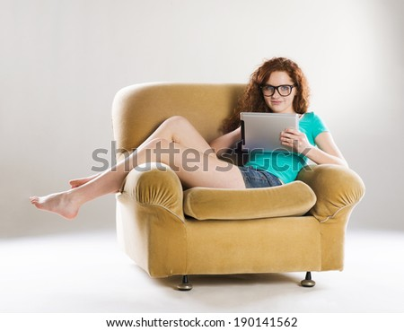 Beautiful girl with digital tablet sitting on armchair, isolated on white background