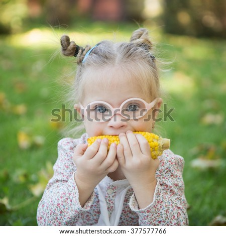 beautiful girl with Down syndrome eating corn on the nature - stock photo