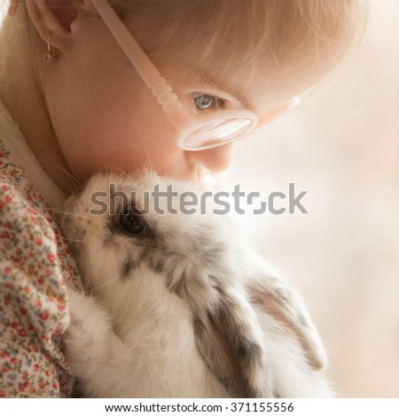 beautiful girl with Down syndrome hugs rabbit - stock photo