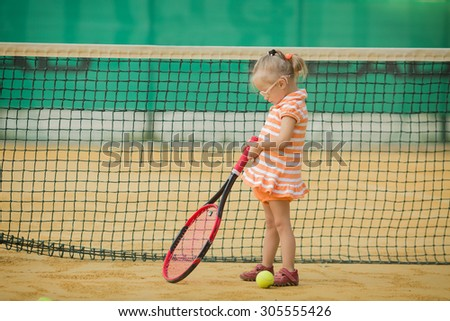 beautiful girl with Down syndrome playing tennis - stock photo