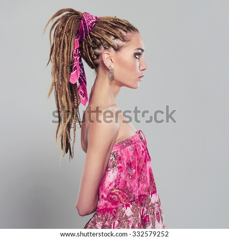 beautiful girl with dreadlocks. pretty young woman with African braids hairstyle. pink dress  - stock photo
