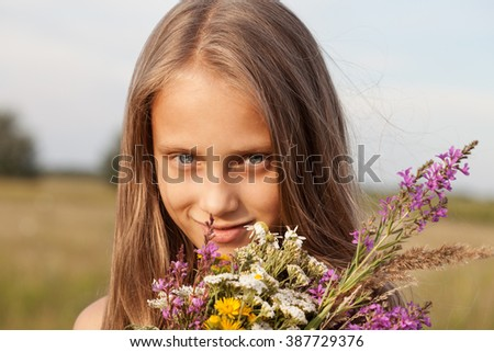 Beautiful Girl with Flowers. Happy Child in Summer. Spring Time. - stock photo