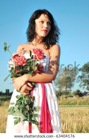beautiful girl with flowers in the field - stock photo