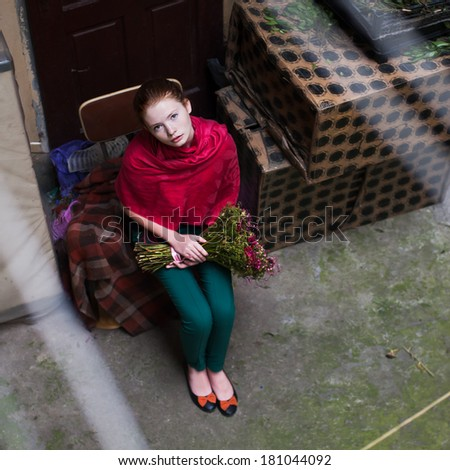 beautiful girl with flowers in the old courtyard cafe - stock photo