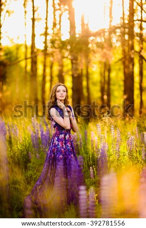 beautiful girl with flowers lupines in a field at sunset