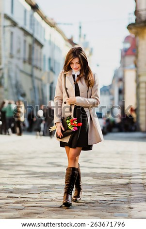 beautiful girl with flowers walking the city - stock photo