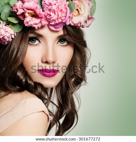 Beautiful Girl with Flowers Wreath. Long Permed Curly Hair and Fashion Makeup. Blossom Portrait of Pretty Young Woman with Pink Flowers.  - stock photo