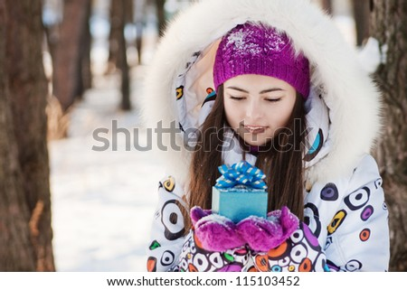 beautiful girl with gift in winter park - stock photo