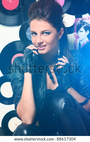 Beautiful girl with headphones in blue highlight against wall with vinyls