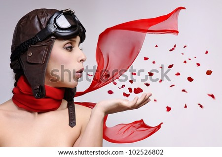 Beautiful girl with helmet and goggles blowing some rose petals - stock photo