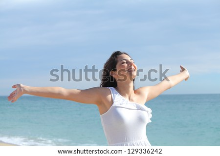 Beautiful girl with her arms raised on the beach with the sea in the background - stock photo