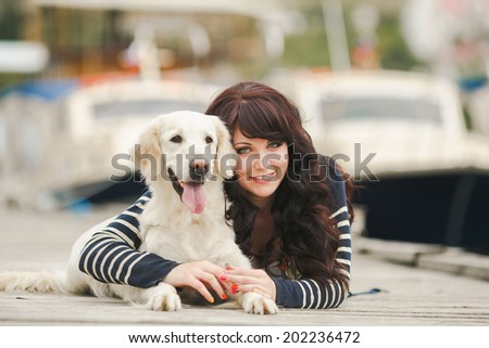 Beautiful girl with her dog near sea. Portrait of young girl with her dog.