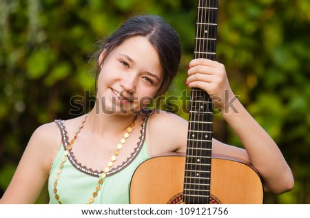 Beautiful girl with her guitar close-up, young musician - stock photo