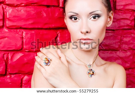 beautiful girl with jewelry on the red backrground